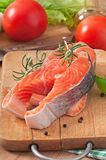 Fresh and raw steaks trout on a wooden cutting board. With sliced lemon, rosemary and pepper Royalty Free Stock Photography