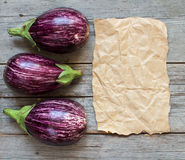 Fresh Raw striped eggplants and craft paper o. N a old wooden table Royalty Free Stock Images