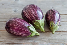 Fresh Raw striped eggplants. Four Fresh Raw striped eggplants on a old wooden table Royalty Free Stock Photography
