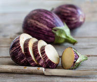 Fresh Raw striped eggplants and slices with knife. On old wooden table Stock Photo