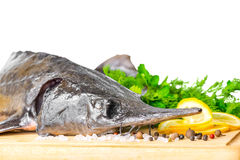 Fresh raw sturgeon fish with greens, lemon, different peppers an Stock Images