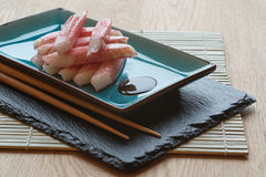 Fresh raw sushi crabsticks on plate with chopsticks Stock Images