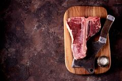 Fresh raw t-bones steak on an olive wooden board with sea salt and a kitchen ax. Top view. Food Stock Photography