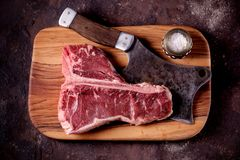 Fresh raw t-bones steak on an olive wooden board with sea salt and a kitchen ax. Top view. Food Stock Photo