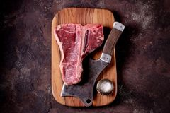 Fresh raw t-bones steak on an olive wooden board with sea salt and a kitchen ax. Top view. Food Royalty Free Stock Images
