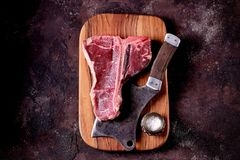 Fresh raw t-bones steak on an olive wooden board with sea salt and a kitchen ax. Top view. Food Royalty Free Stock Image
