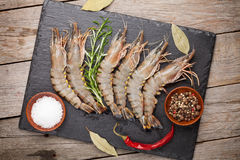 Fresh raw tiger prawns and spices. On  black stone plate over wooden table Stock Photography