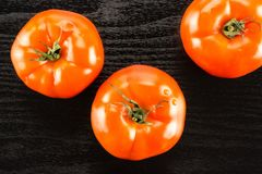 Fresh Raw tomato La parcela variety on black wood. Three red tomato isolated on black wood background top view Royalty Free Stock Photos