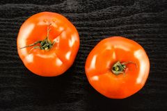 Fresh Raw tomato La parcela variety on black wood. Two red tomato isolated on black wood background top view Stock Image