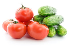 Fresh raw tomatoes and cucumbers. Fresh raw tomatoes and cucumbers over a white background Stock Photography