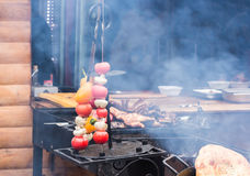 Fresh raw tomatoes onion mushroom eggplant on skewers over charcoal  grid  brazier grill. Fresh raw tomatoes onion mushroom eggplant on skewers over charcoal on Stock Photo