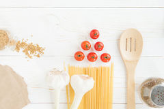 Fresh raw tomatoes with pasta, garlic and wooden spoon on table. Top view of fresh raw tomatoes with pasta, garlic and wooden spoon on table Royalty Free Stock Images