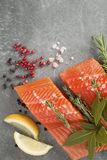 Fresh Raw Trout Fillets with Herbs and Spices. Selection of Herbs and Spices with fresh fillets of raw pink trout on a grey slate background. Ingredients Royalty Free Stock Photography