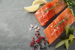 Fresh Raw Trout Fillets with Herbs and Spices. Selection of Herbs and Spices with fresh fillets of raw pink trout on a grey slate background. Ingredients Royalty Free Stock Photo