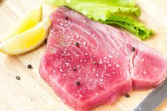 Fresh raw tuna fillet with black pepper corns, salt, lemon and olive oil on rustic background. Raw tuna steak on wooden cutboard,. Close up, selective focus Royalty Free Stock Photography