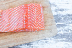 Fresh raw uncooked salmon fish piece over wooden board Royalty Free Stock Photography