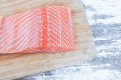 fresh raw uncooked salmon fish piece over wooden board Stock Photography