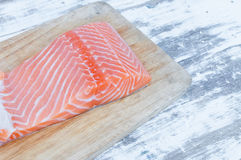 Fresh raw uncooked salmon fish piece over wooden board Royalty Free Stock Photos