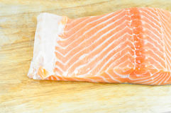 Fresh raw uncooked salmon fish piece over wooden board Royalty Free Stock Image