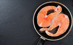 Fresh raw unprepared fish salmon or trout, steaks, in a frying pan, top view. Close-up of raw pink salmon steaks in a frying pan, top view Stock Photos