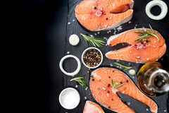 Fresh raw unprepared fish salmon or trout, steaks, in a skillet for cooking, with salt, pepper On black stone concrete table, copy. Space top close view Royalty Free Stock Image