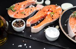 Fresh raw unprepared fish salmon or trout, steaks, in a skillet for cooking, with salt, pepper On black stone concrete table, copy. Space top close view Stock Image