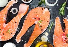 Fresh raw unprepared fish salmon or trout, steaks, in a skillet for cooking, with salt, pepper On black stone concrete table, copy. Space top close view Stock Photos