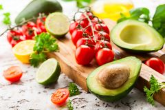 Avocado, cherry tomatoes, citrus and fresh herbs royalty free stock photography
