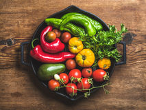 Fresh raw vegetable ingredients for healthy cooking or salad making in black grilling iron pan over rustic wooden. Background, top view, horizontal composition Stock Image
