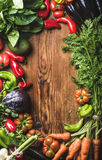 Fresh raw vegetable ingredients for healthy cooking or salad making over rustic wood background, top view, copy space. Vertical composition. Diet or vegetarian Royalty Free Stock Photos