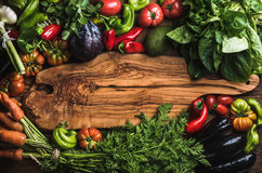 Fresh raw vegetable ingredients for healthy cooking or salad making with rustic olive wood board in center. Top view, copy space. Diet or vegetarian food Royalty Free Stock Images