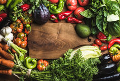 Fresh raw vegetable ingredients for healthy cooking. Or salad making with rustic wood board in center, top view, copy space, horizontal composition. Diet or Royalty Free Stock Photography