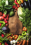 Fresh raw vegetable ingredients for healthy cooking or salad making with rustic wood board in center, top view, copy. Space, vertical composition. Diet or Royalty Free Stock Photography
