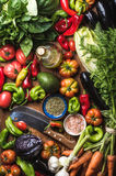 Fresh raw vegetable ingredients for healthy cooking or salad making, top view. Olive oil in bottle, spices and knife Stock Photo