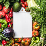 Fresh raw vegetable ingredients for healthy cooking or salad making with white ceramic board in center over wooden. Background, top view, copy space, vertical Royalty Free Stock Photos