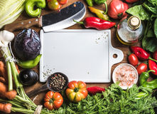 Fresh raw vegetable ingredients for healthy cooking or salad making with white ceramic board in center, top view, copy. Fresh raw vegetable ingredients for Royalty Free Stock Photo