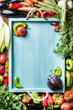 Fresh raw vegetable ingredients for healthy cooking or salad making on wooden background and blue  tray in center, top. Fresh raw vegetable ingredients for Royalty Free Stock Photos