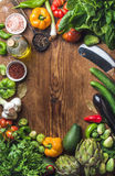 Fresh raw vegetable ingredients for healthy cooking or salad making on wooden background, copy space in center, top view. Vertical composition. Diet or Stock Image