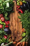 Fresh raw vegetable ingredients for healthy cooking or salad making on wooden background with rustic board in center. Fresh raw vegetable ingredients for healthy Stock Images