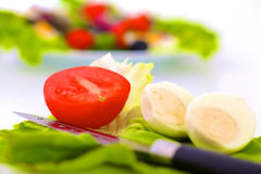 Fresh raw vegetable salad with tomatoes and green lettuce on wooden plate isolated over white background.  Stock Photos