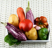 Fresh Raw Vegetables. Arrangement of Fresh Raw Vegetables with Striped Eggplants, Green and Red Tomatoes, Potato, Carrot and Garlic on Wooden Tray closeup on Royalty Free Stock Photo