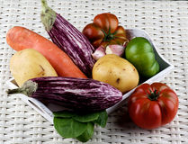 Fresh Raw Vegetables. Arrangement of Fresh Raw Vegetables with Striped Eggplants, Potato, Carrot, Green and Red Tomatoes, and Garlic on Wooden Tray closeup on Royalty Free Stock Photos