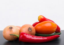 Fresh raw vegetables on black surface on white background Royalty Free Stock Photo