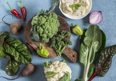 Fresh raw vegetables - broccoli, cauliflower, chard, peppers, beets, onions on a blue background. Top view Stock Image
