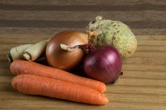 Fresh raw vegetables, carrot, onion, celery and parsley root on the cod board and brown tablecloth. stock photography
