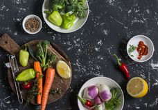 Fresh raw vegetables - carrots, peppers, broccoli, turnips, spices and herbs on dark background, top view. Cooking ingredients Stock Photos