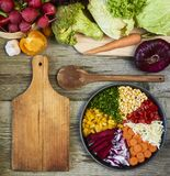 Fresh raw vegetables with cutting board on wooden background cop royalty free stock images