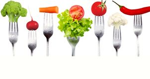 Fresh raw vegetables on forks on white background. Fresh raw vegetables forks green red white Stock Photos