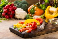 Fresh raw vegetables. Fresh picked organic red, yellow and green bell pepper cut into pieces on old wooden board and assorted vegetables. Healthy food concept Royalty Free Stock Image