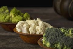 Fresh Raw Vegetables. Fresh pieces of romanesco broccoli, broccoli and cauliflower in small rustic wooden bowls. Selective focus on the cauliflower Stock Photo